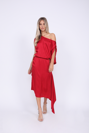 Model is wearing the Hayley Asymmetric Shoulder Dress in red, belted at the waist with matching sash, and open toe, ankle strap, nude color high heels.