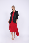 Model is wearing the Hayley Asymmetric Shoulder Dress in red, belted at the waist with matching sash, and the Hayley Blazer in black on top, unbuttoned. Also worn with open toe, ankle strap, nude color high heels.