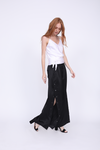 Model is wearing the Aimee Camisole in bright white, with sash tied around the waist. Worn with Hayley Wide Leg Snap Pant in black and black high heels.