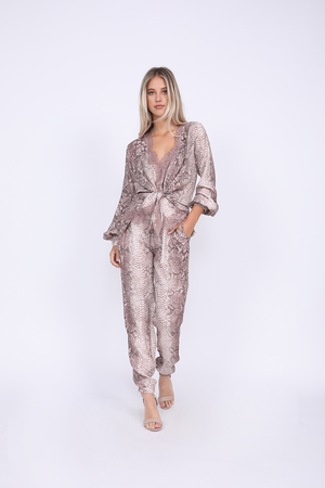 Model is wearing the Python Print Pant in muted rose python along with the Python Wrap Top in muted rose python, worn tied at the front waist. Also worn with open toe, ankle strap, nude high heels.