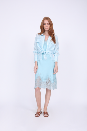 Model is wearing the Anne Marie Shirt in baby blue/off white, unbuttoned, cuffed, and tied at the front, with the Coco Bodice Lace Dress in Aqua Powder underneath. Worn with brown, flat sandals.