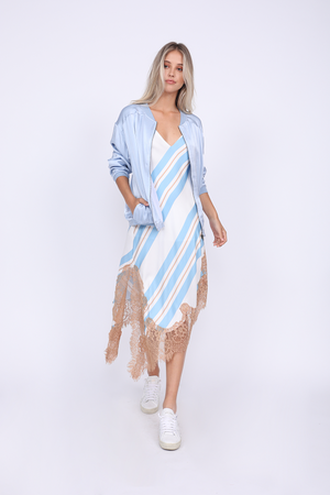Model is wearing the Bold Stripe Dress in baby blue with the Hayley Bomber Jacket in baby blue and white sneakers.
