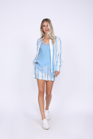 Model is wearing the Bold Stripe Shirt in baby blue, unbuttoned, with the Coco Lace Silk Cami in baby blue underneath, and the Bold Stripe Shorts in baby blue. Worn with white sneakers.