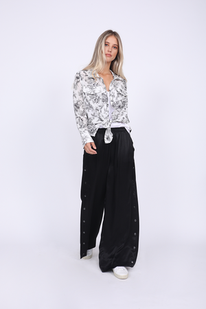 Model is wearing the Hayley Wide Leg Snap Pant in black with the Provence Shirt in black provence toile tied at the front waist and with the Hayley Camisole in bright white underneath, tucked in. Also worn with white sneakers.