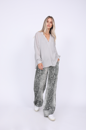 Model is wearing the Python Silk Print Wide Leg Pants in grey python with the Stretch Long Sleeve Tee in ice grey. Worn with white sneakers.