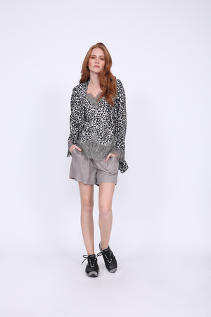 Model is wearing the Tencel Paperbag Short in steeple grey with the Animal Print Wrap Top in grey leopard animal print worn open and the Silk Print Racerback Lace Cami in grey leopard animal print. Also worn with black sneakers.