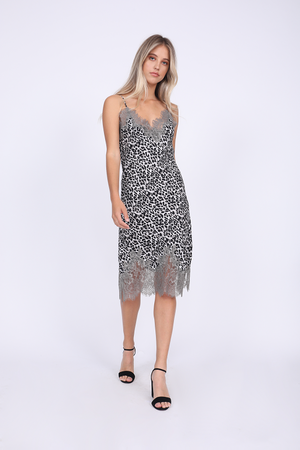 Model is wearing the Coco Print Silk Slip Dress in grey animal with open toe, ankle strap black high heels.