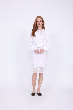 Model is wearing the Silk Wrap Top in bright white, tied at the front waist, with the Zoe Coco Dress in white underneath. Worn with flat, open toe, slip in sandals.