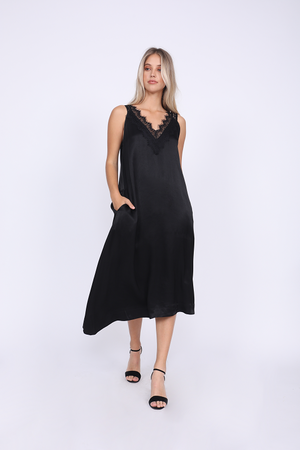 Model is wearing the Hayley Asymmetric Dress in black with open toe, ankle strap, black high heels.