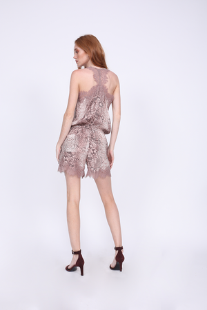 Back View; Model is wearing the Python Romper in muted rose python with open toe, ankle strap, burgundy velvet high heels.