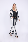 Model is wearing the Hayley Camisole in black, belted at the waist with a gold chain. Also worn with the Bold Stripe Pant in black, the Bold Stripe Shirt in black, and open toe, ankle strap, black high heels.