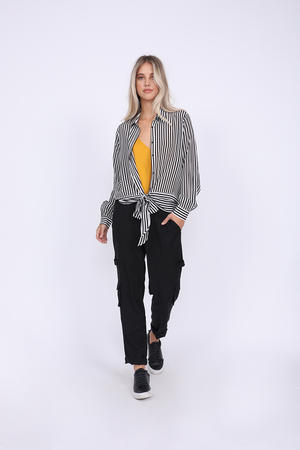 Model is wearing the Mini Stripe Shirt in black, unbuttoned and tied at front waist, with the Double Silk Solid Cami in gold underneath, tucked in, and the Tencel Cargo Pant in black. Also worn with black sneakers.