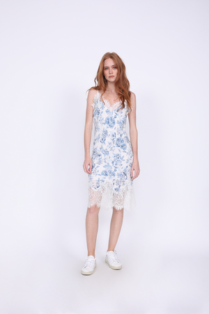 Model is wearing the Provence Slip Dress in navy provence toile with white sneakers.