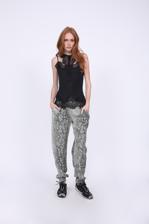 Model is wearing the Zoe Coco Camisole in black with the Python Print Pant in grey python. Also worn with black sneakers.