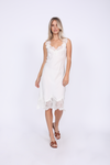 Model is wearing the Megan Coco Dress in white with brown, slip in, flat, open toe sandals.