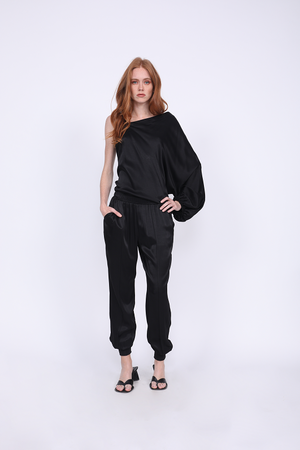 Model is wearing the Hayley Jogger in black with the Hayley One Shoulder Top in black. Also worn with kitten heel, black, slip in thong sandals.