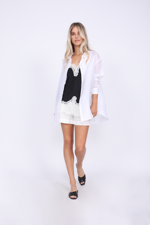 Model is wearing the Megan Camisole in black with dove lace, along with the Tencel Paperbag Short in white, and the Shirred Back Shirt in white, worn unbuttoned. Also worn with black, flat, slip in, open toe sandals.