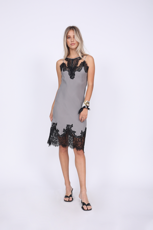 Model is wearing the Zoe Coco Dress in steeple grey with black lace. Worn with low heeled, black, thong style sandals and a silk ascot worn around the wrist.