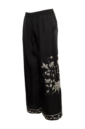 The Emily Silk Embroidered Pants in black with white embroidery; side view.