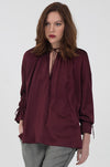 Model is wearing the Pleasant Wrap Front Tie Top in burgundy with the Menswear Plaid Pants in grey.