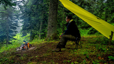 Man sitting beside campfire under tarp in the woods.