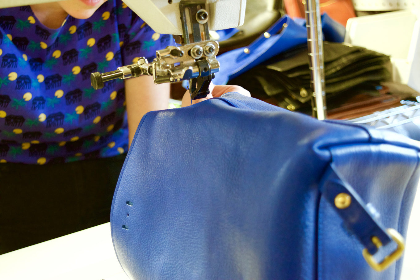 stitching the Lotuff Leather Mini Sling in electric blue