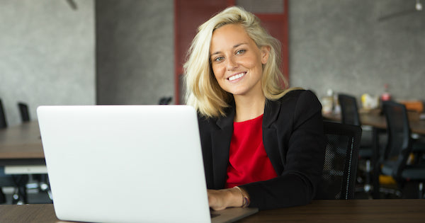 woman with blonde hair typing with laptop