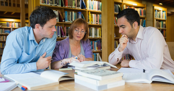 three people reading inside a library