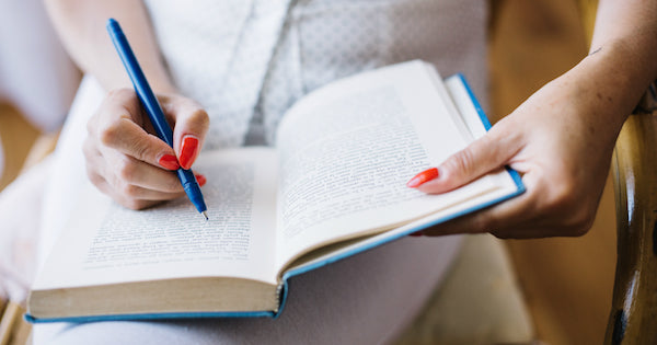 blue pen being held over an open book