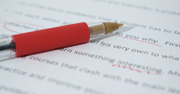 proofreading a paper with a red pen