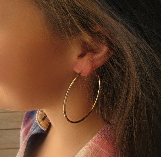 Model wearing 3 inch gold plain hoop earrings