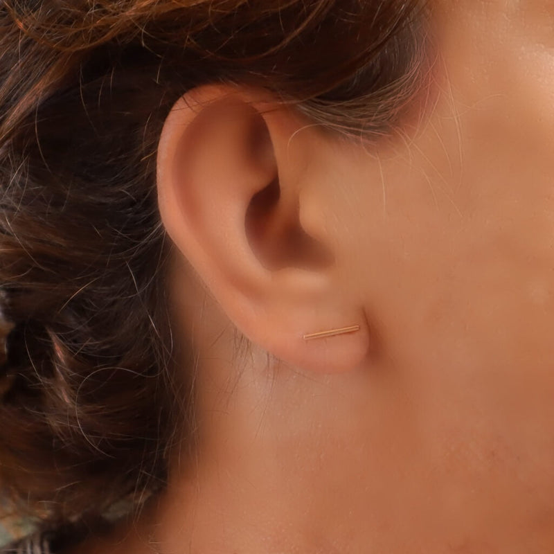 model wearing gold bar stud earrings