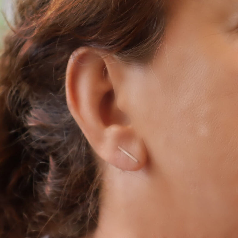 model wearing pink gold bar stud earrings