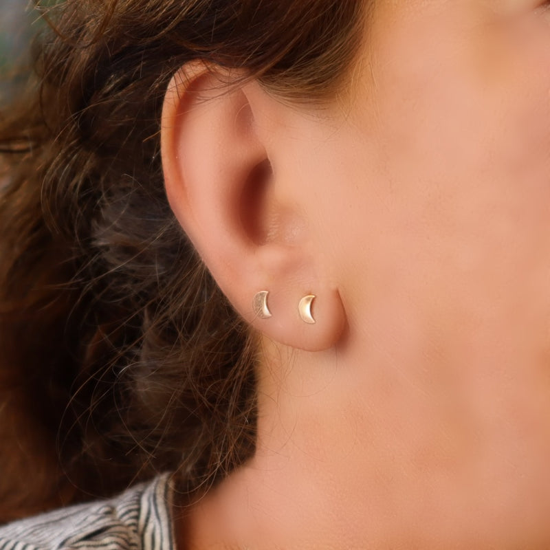 model wearing two crescent moon stud earrings in gold