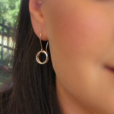 model wearing gold yin & yang earrings