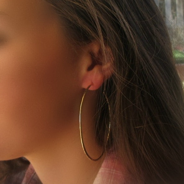 model wearing 3 inch thick gold hammered hoop earrings