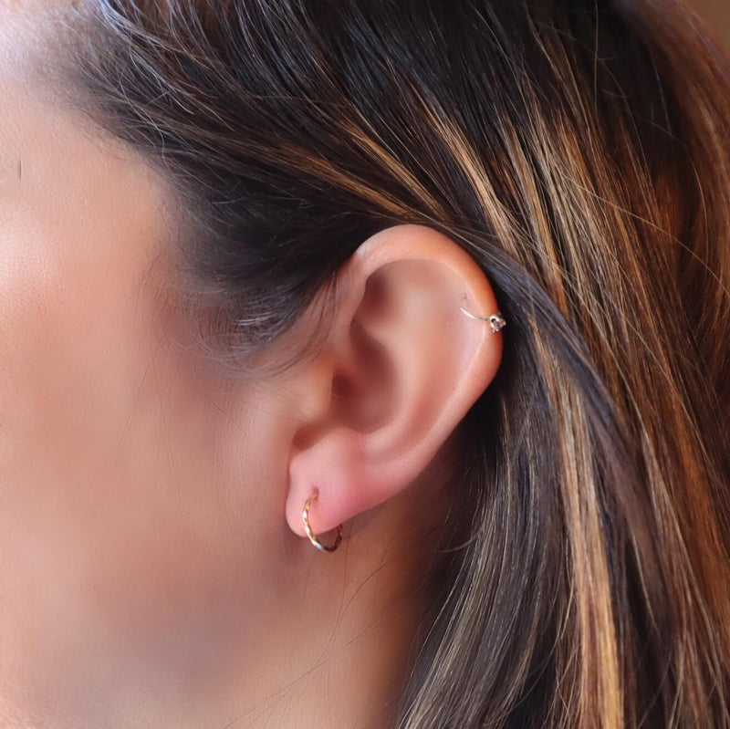 model wearing tiny gold twist hoop earring