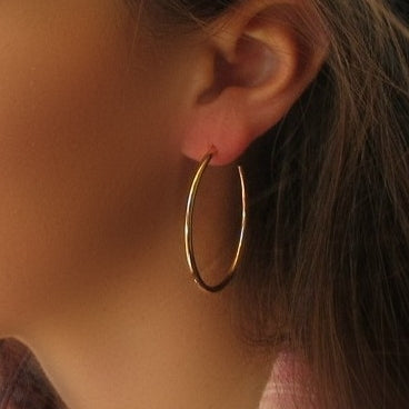 model wearing oval pink gold hoop earrings
