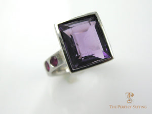 Large amethyst bezel set in 14K white gold with ruby accents