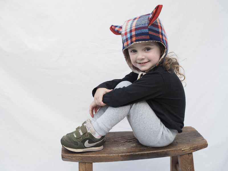 cheeky little girl sitting on a step, keeping warm in her plaid winter kids hat