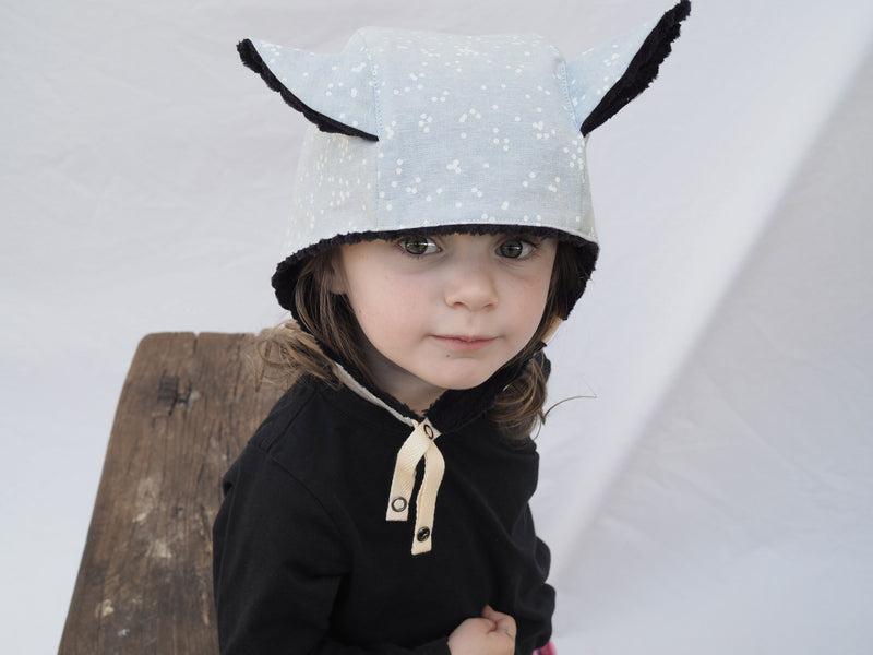 snow blue warm winter kids bonnet with contrasting black fluffy lining and cute animal ears