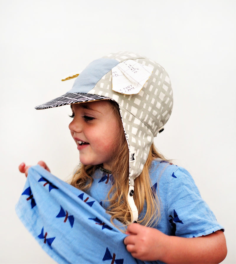 trendy kids sun hat with five panels, pleated animal ears, a blue front patch and taupe and white print.