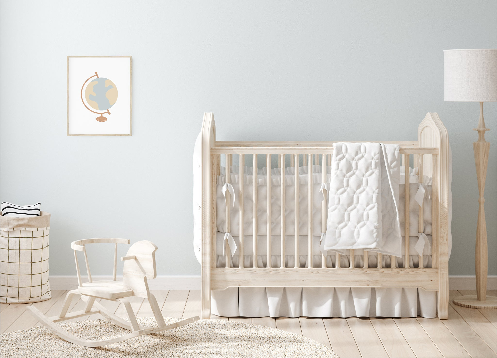 Baby nursery with blue wall, light wood furniture, and globe artwork