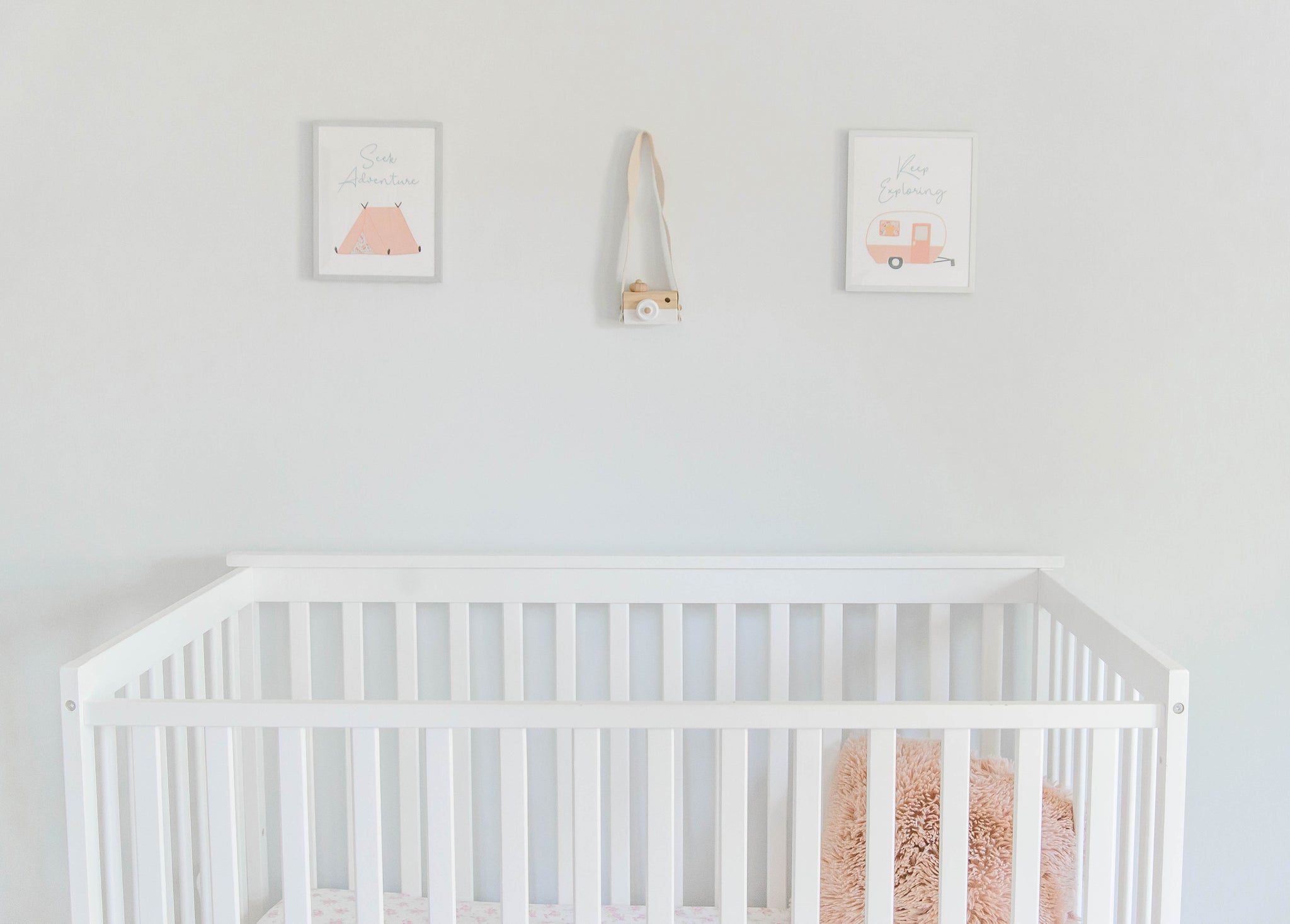 Pastel pink and white nursery with camping wall art