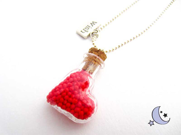 Heart glass bottle filled with red dots. Bottle necklace