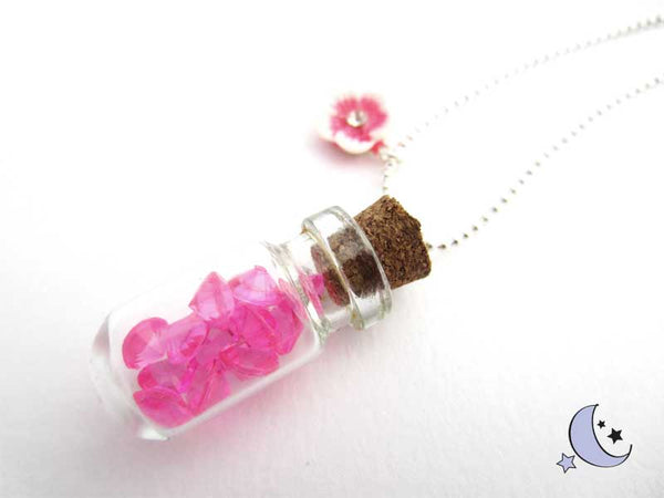 Miniature glass bottle charm, with pink rhinestones.