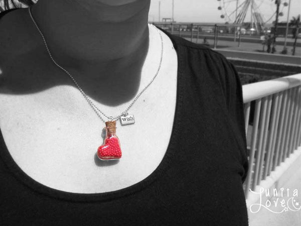 Bottle pendant. Heart shape. Mounted in necklace. Vial necklace