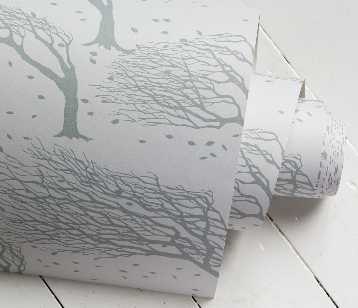 'Northeasterly' Windswept Trees Wallpaper in Soft Grey