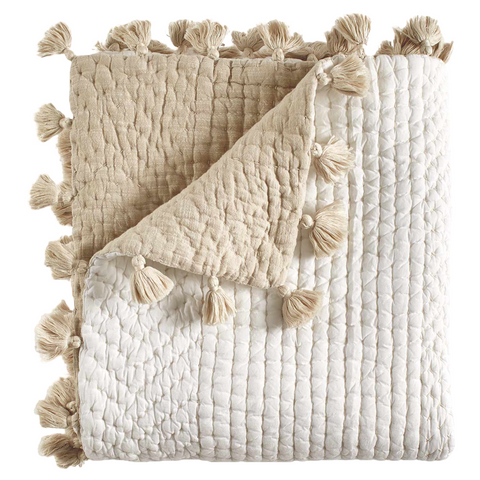 Image of folded ivory and beige quilted blanket with sand colored tassels