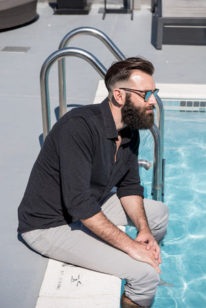 man with beard sitting by the pool
